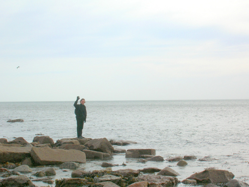Photograph: Ed stands waving on a rock, quite pleased with himself